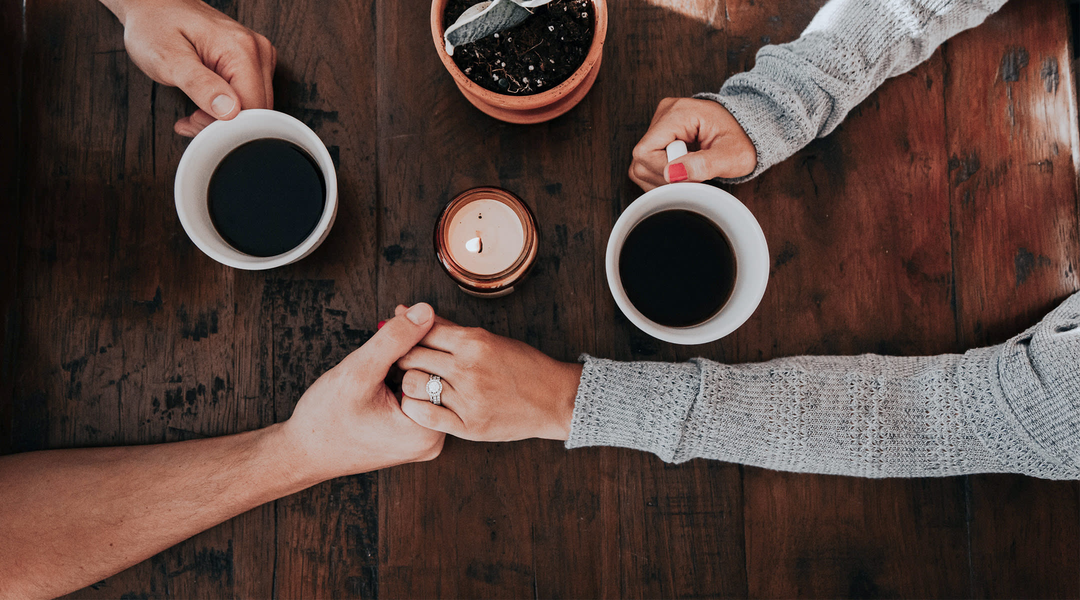 sad couple holding hands across table with coffee