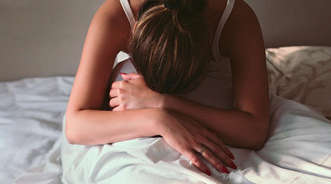 pregnant woman on her bed with severe morning sickness