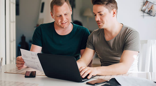 Same sex couple looks at laptop computer together