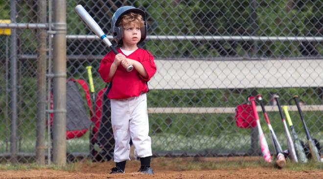 small child playing baseball at bat