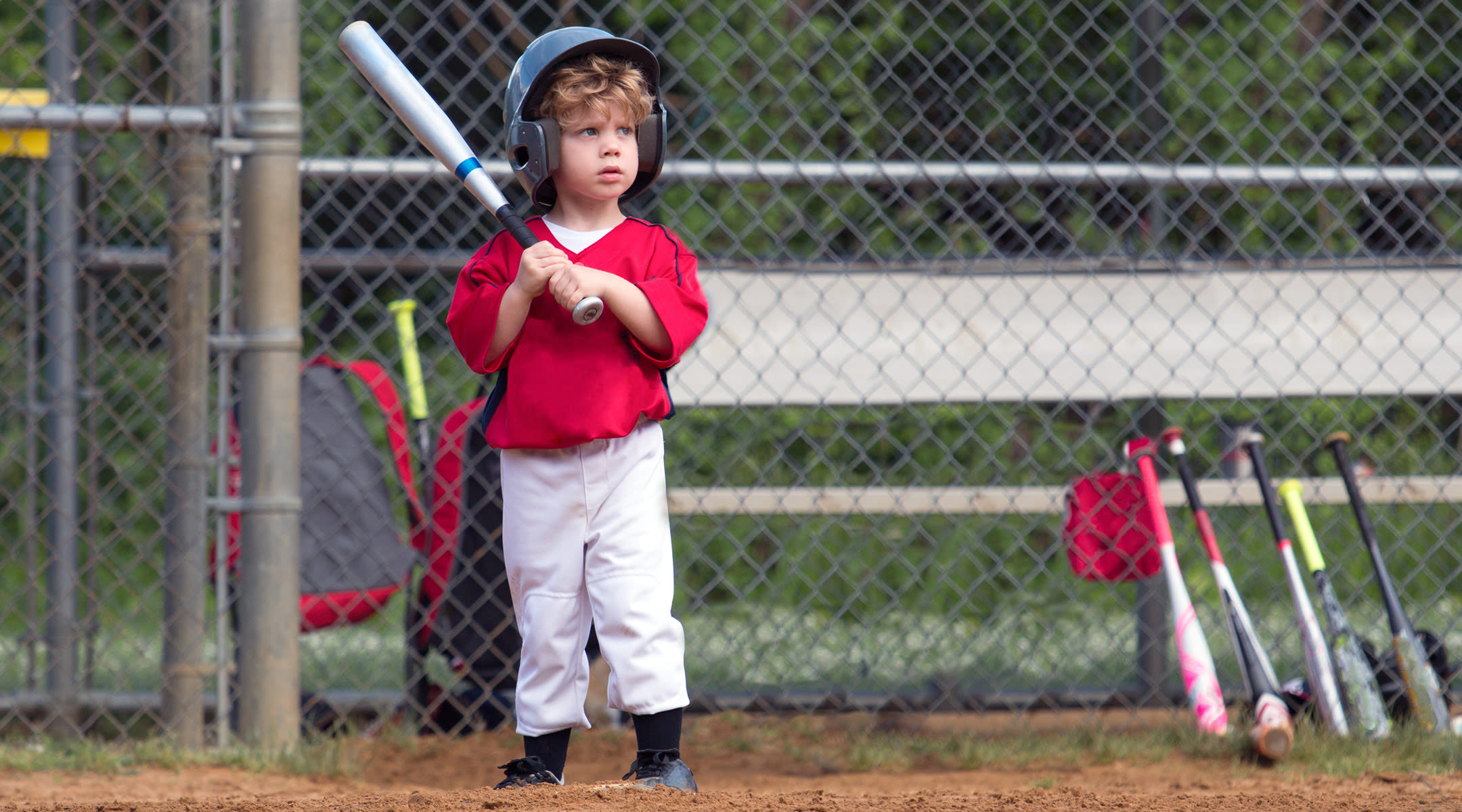 small child playing baseball at bat