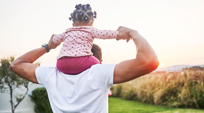 Dad holds his toddler daughter on his shoulders while looking out over an outdoor landscape.