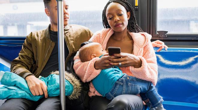 breastfeeding mom on public bus on her phone