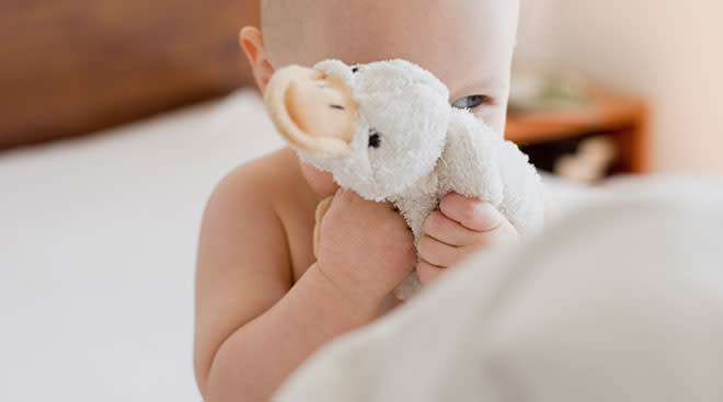 Baby holding duck stuffed animal by its face and smiling.