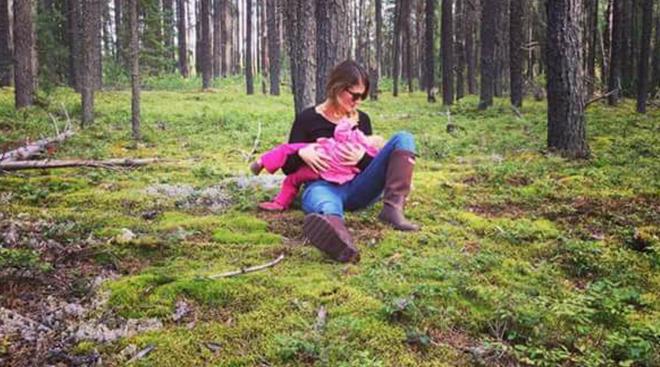 Woman nursing her toddler under a tree