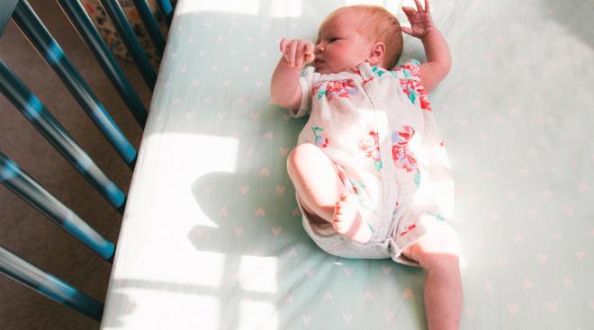 newborn baby laying in crib with heart mattress