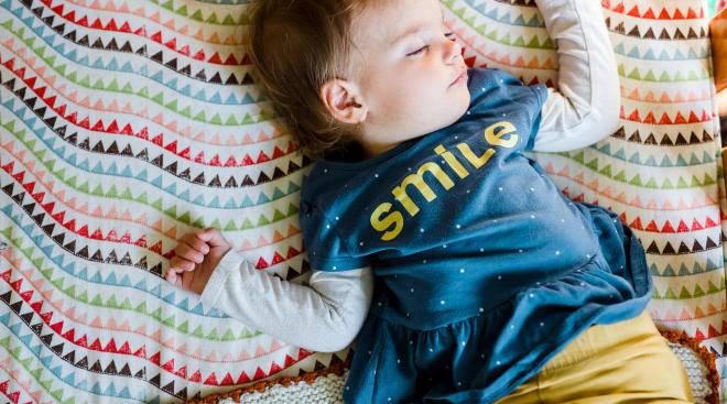 toddler sleeping in her crib