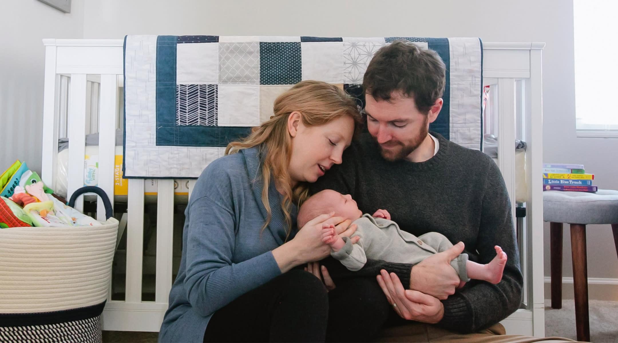 parents stare at newborn baby in their nursery