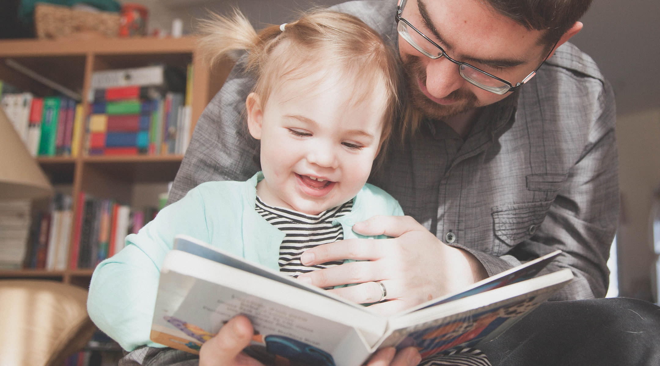 father holding toddler daughter with book