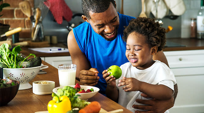 Happy dad helping his son have a healthy snack of a green apple.