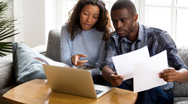 couple looking at bills on laptop together