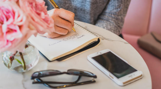 woman writing in notebook with her cell phone nearby