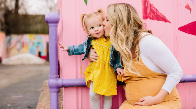 mom kissing her toddler daughter in front of painted mural background