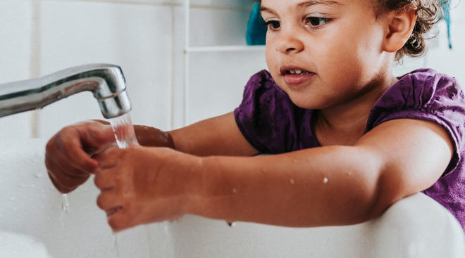 toddler washes hands in sink