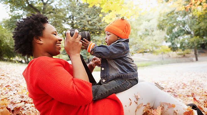 mom taking photos of her baby during the fall season