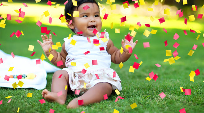happy baby with arms up and confetti falling