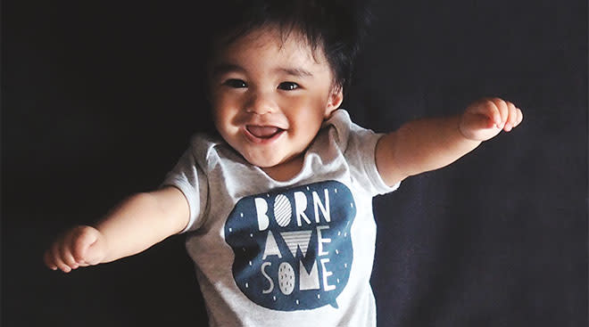 """Happy baby wearing a onesie thats """"born awesome."""""""