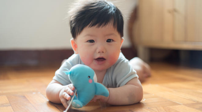 baby holding toy during tummy time