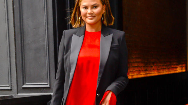 chrissy teigen in red dress walking otuside