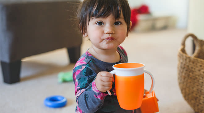 toddler child holding orange sip cup