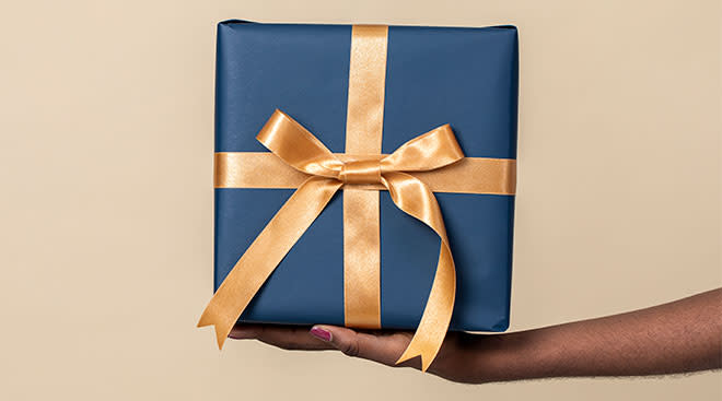 hand holding out beautifully wrapped gift