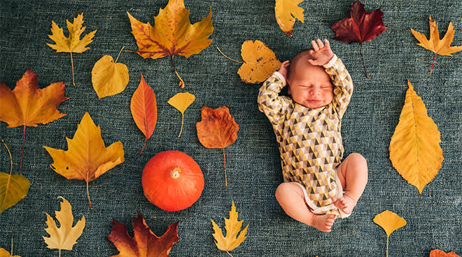 newborn baby photographed with fall leaves and a pumpkin