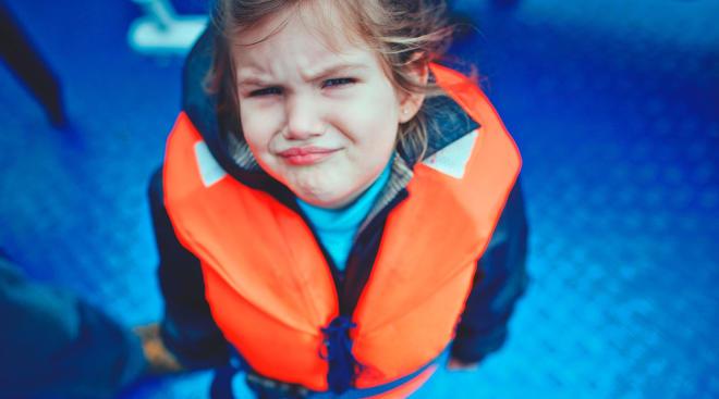 sad toddler wearing life vest