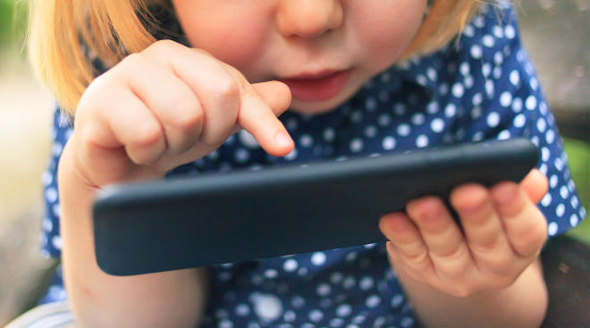 toddler girl intently uses a mobile phone