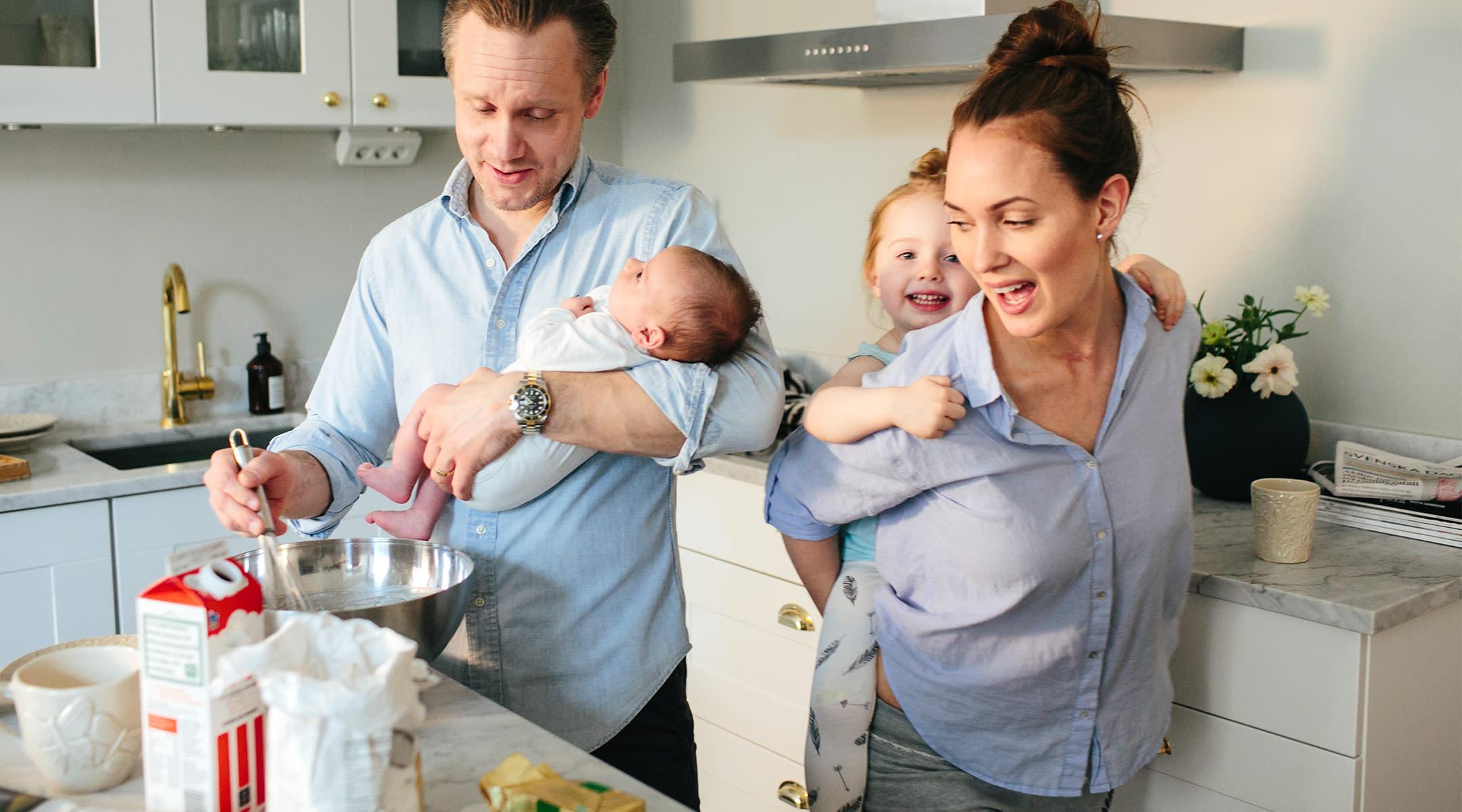 parents entertain hyper children in their kitchen while cooking