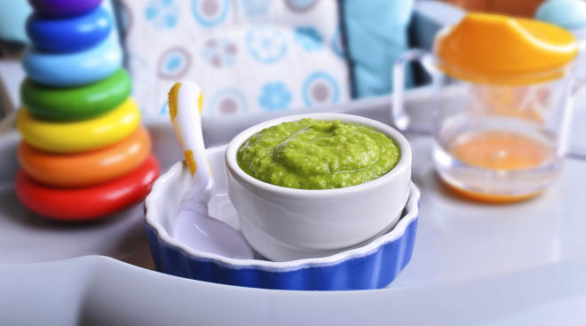 Detail of green baby food in bowl on high chair.