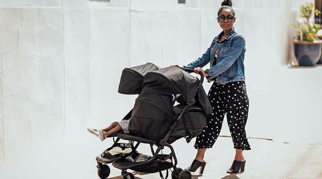 stylish mom pushing double baby stroller
