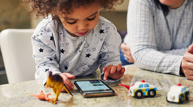 toddler boy playing with mobile phone screen