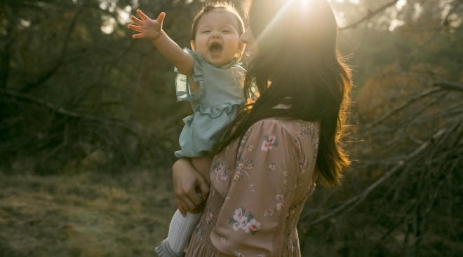 happy one year old girl held by her mom