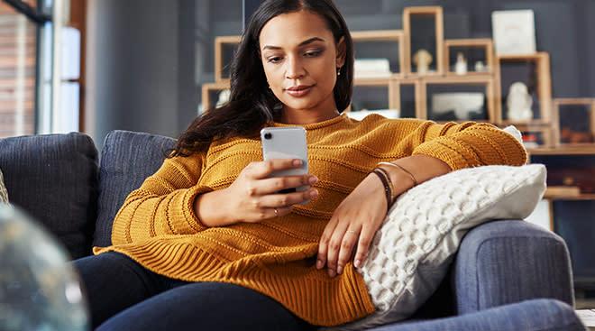 sad woman at home looking at her phone
