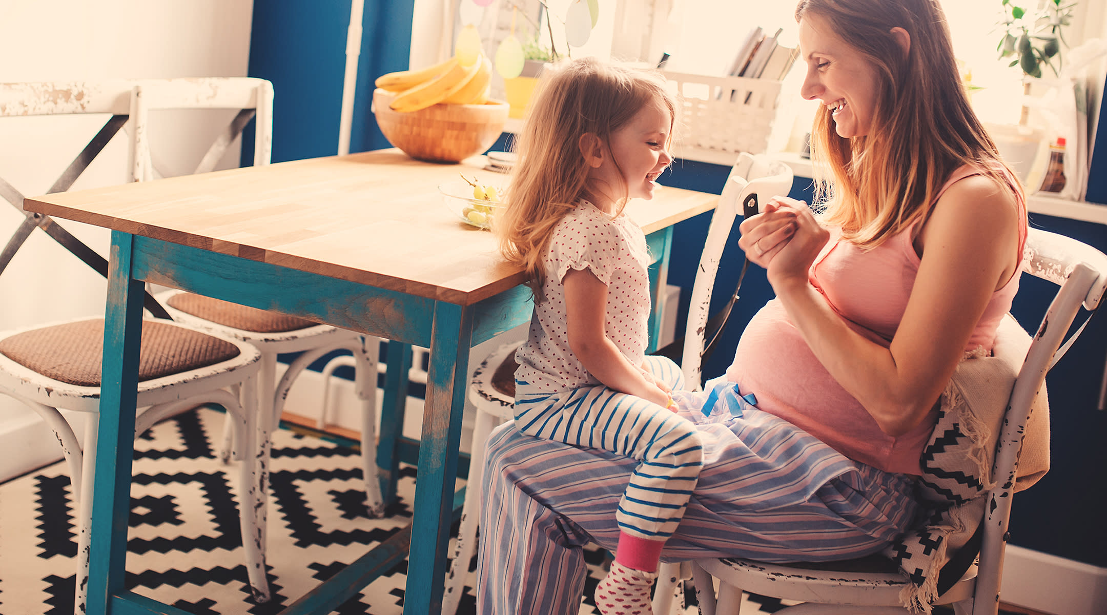 Young girl sitting on pregnant mom's lap in the kitchen