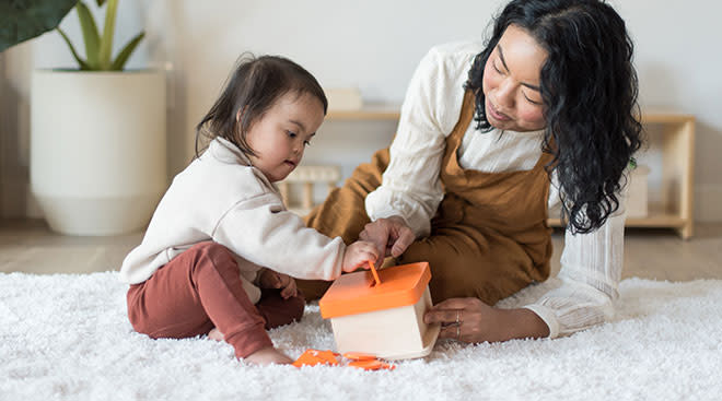Child with special needs and her mom playing with montessori toys.
