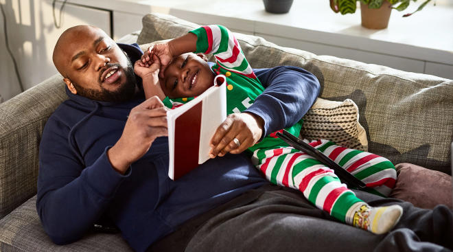 dad reading book to his son during the holidays