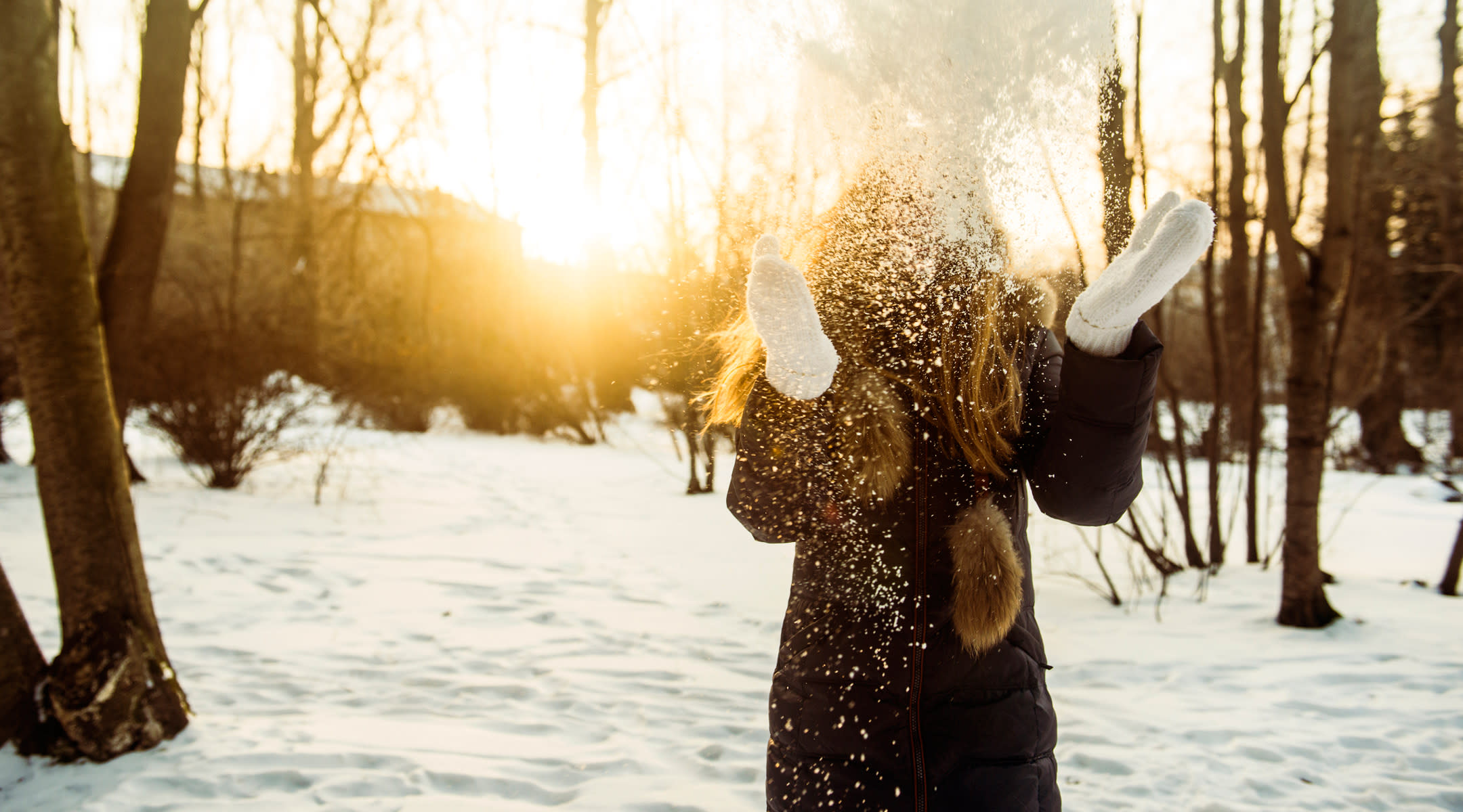 Woman throwing snowball into the air with snowy trees in the background.