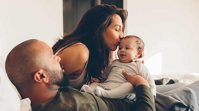 mother and father holding baby