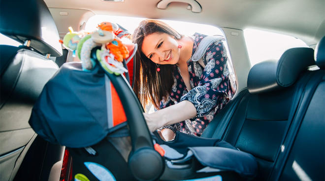 mom buckling her baby into infant car seat