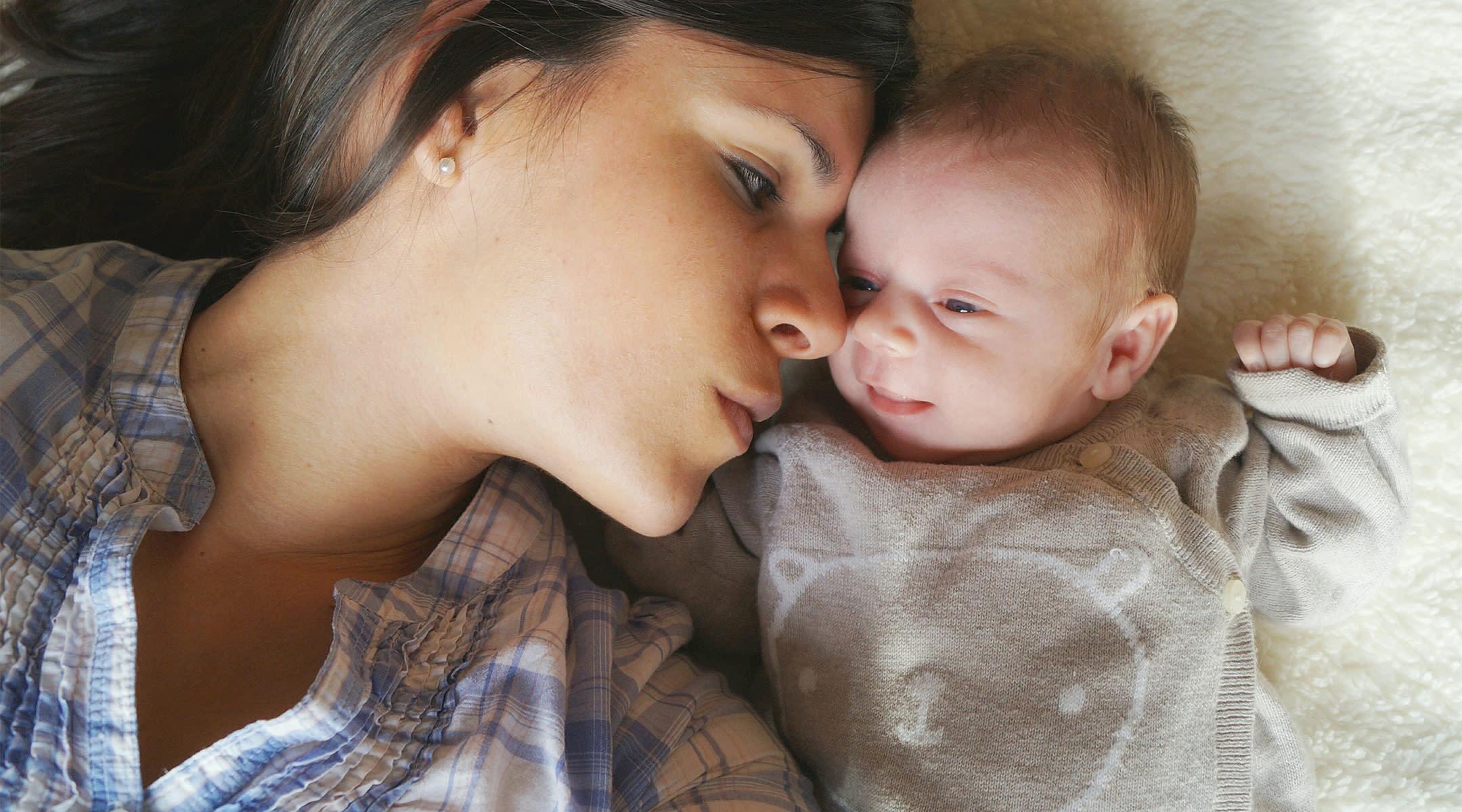 new mom snuggles her newborn baby