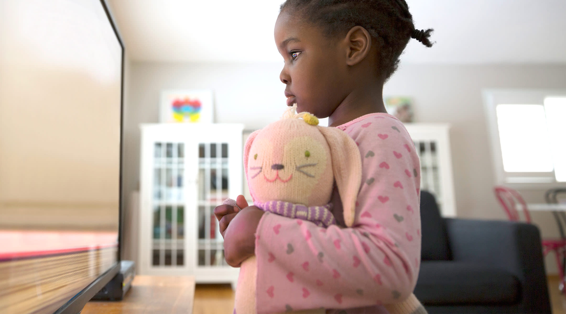 preschool age girl standing and watching tv