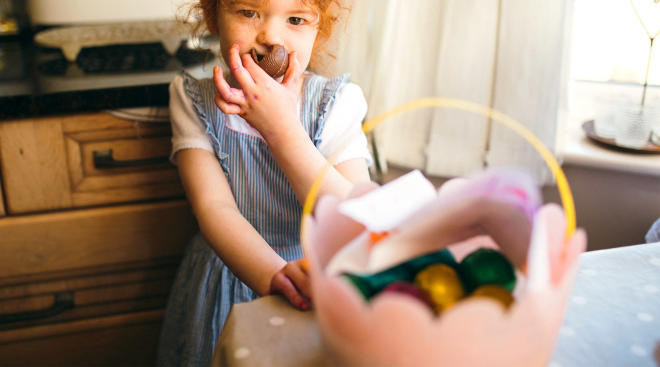 little girl eating her easter basket chocolate