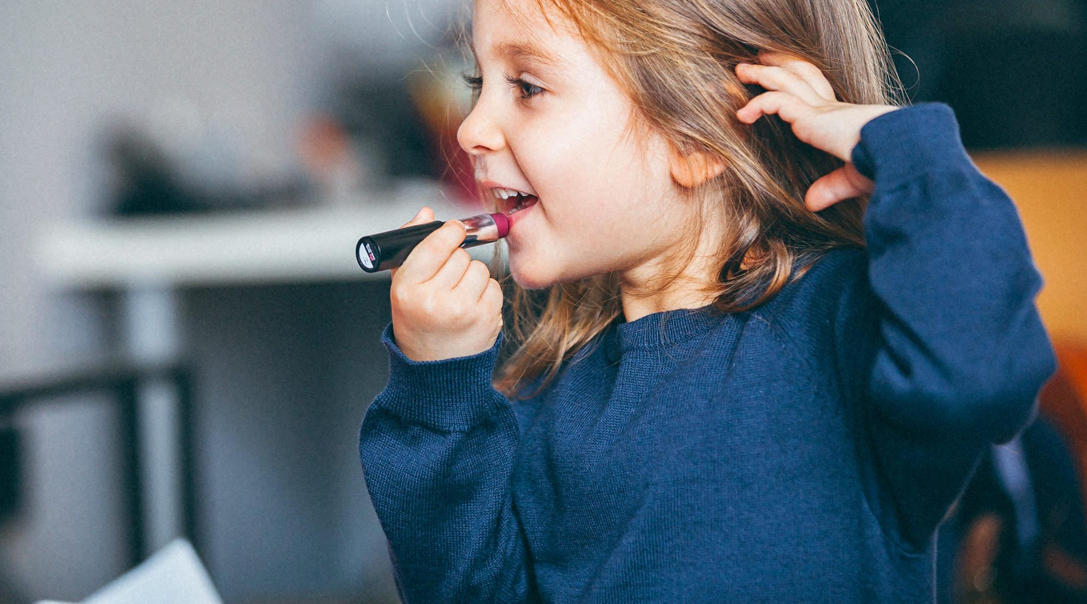 toddler girl putting on lipstick