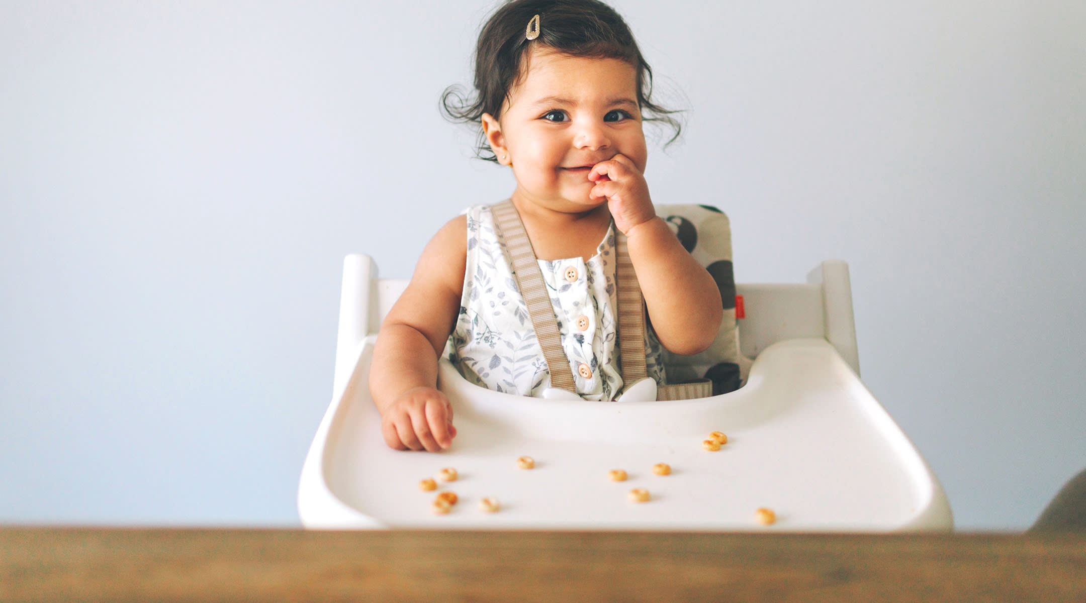 happy baby eating solid foods in high chair