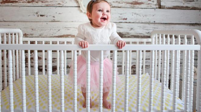 baby girl standing in her crib in her nursery