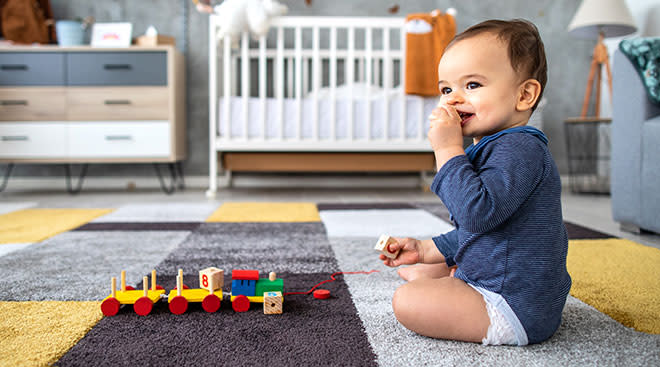 Happy baby playing with a toy train in his nursery.