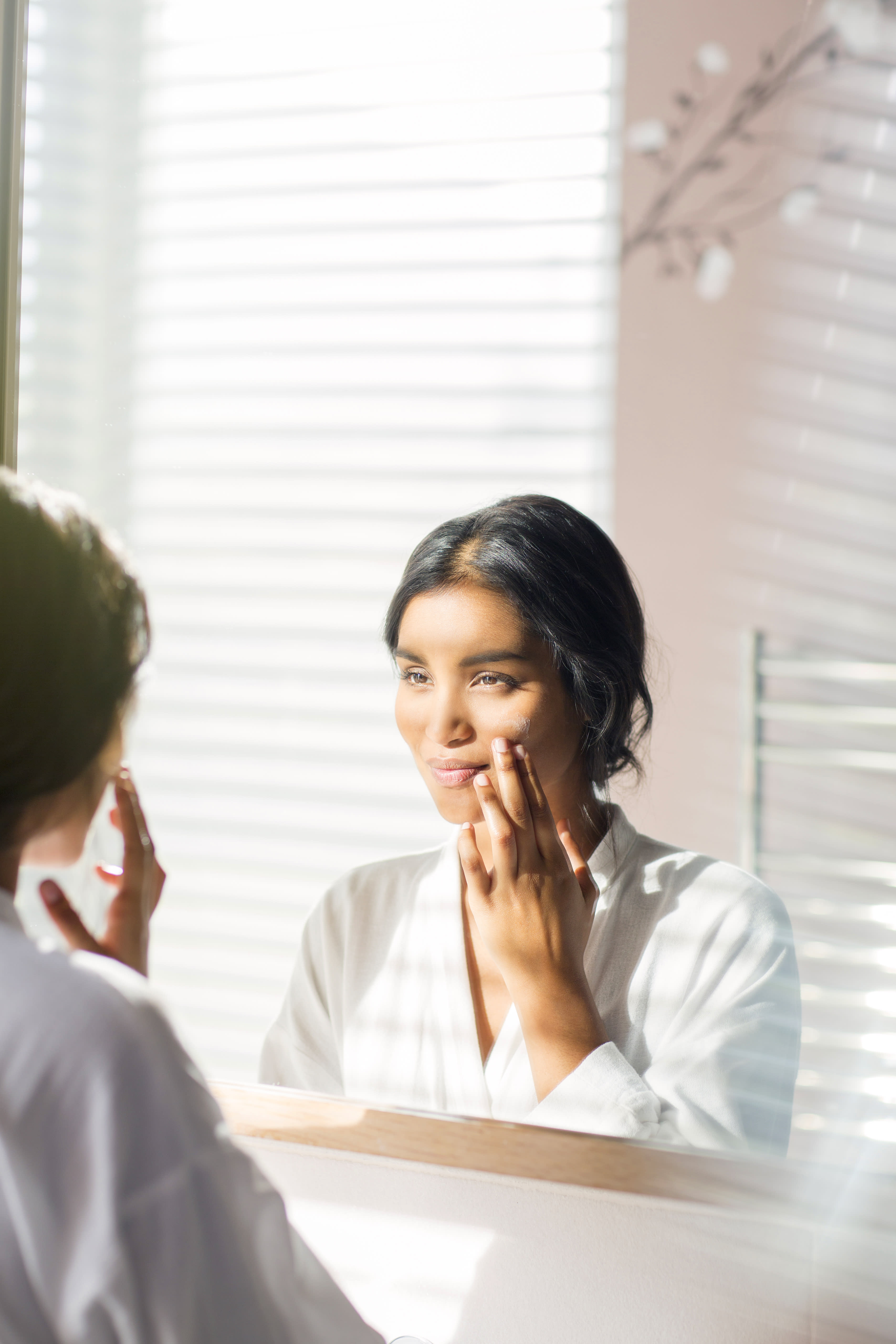 Woman's reflection in bathroom mirror applying skincare product.