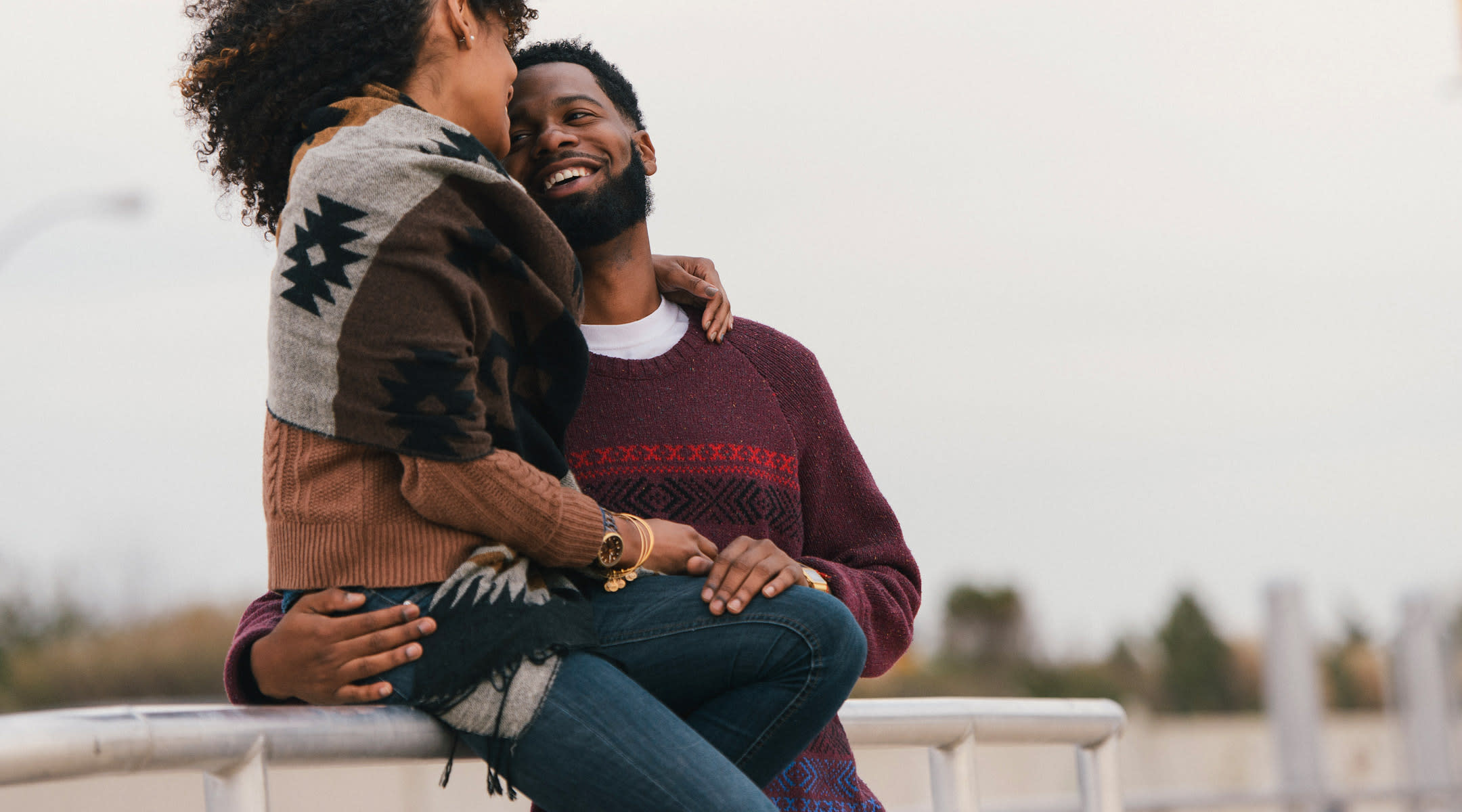 African American couple embracing outside.