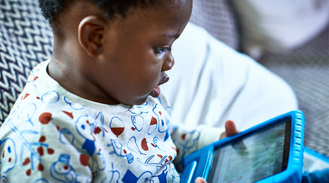 toddler at home watching screen on tablet